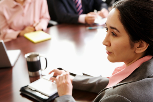 Businesswoman sitting with business executives in board room